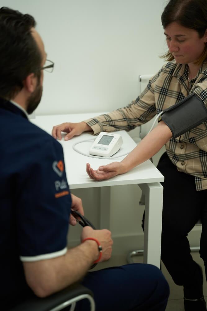 Pacijentkinja i doktor u toku pregleda. Merenje krvnog pritiska.