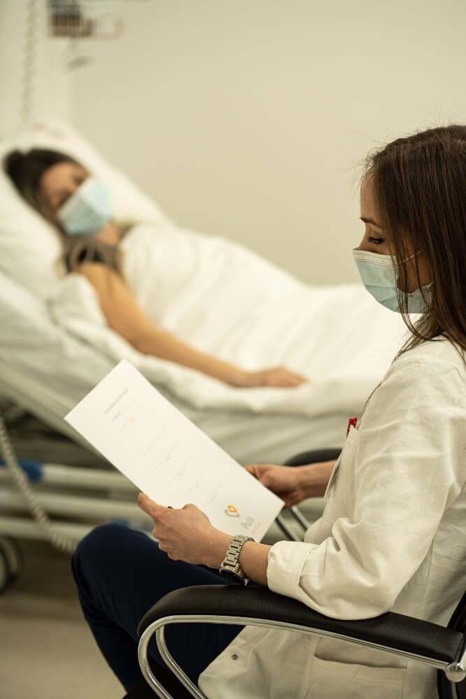 Pacijentkinj leži u krevetu na klinici dok doktorka pregleda rezultate