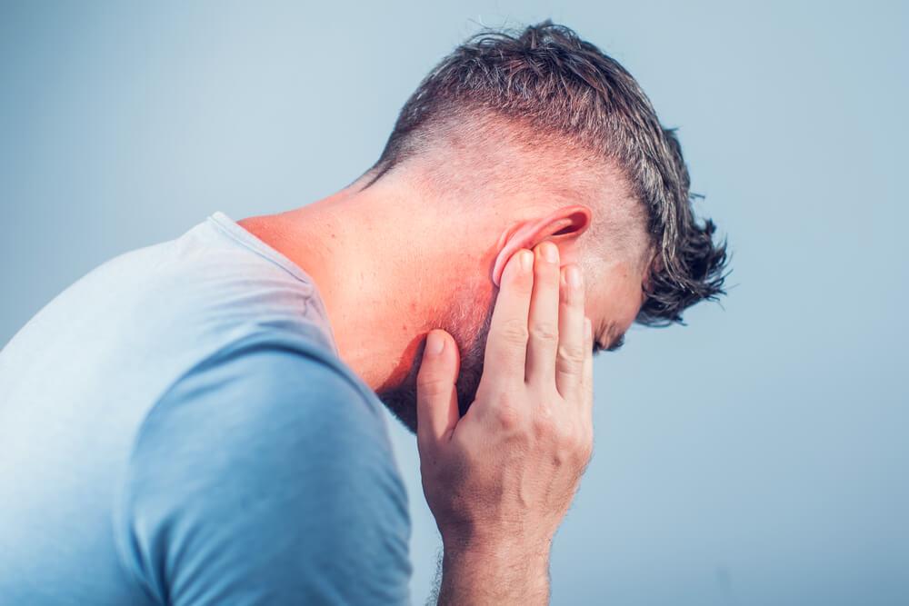 Čovek koji oseća bol u uhu