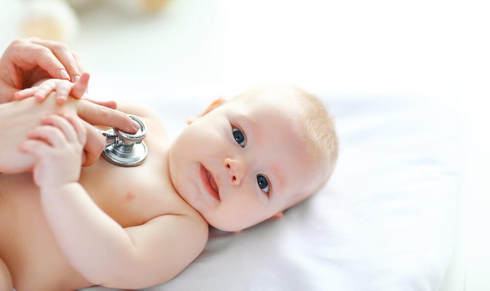Pedijatar sluša srce novorođenčeta uz pomoć stetoskopa