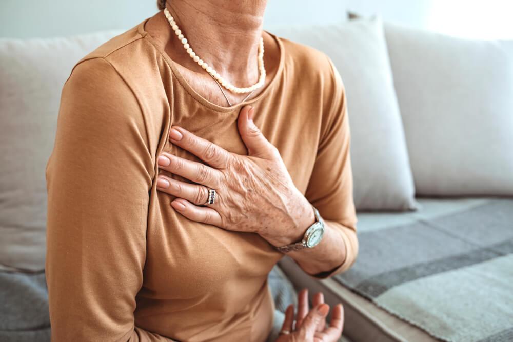 Starija žena drži ruku na grudima usled bolnog osećaja